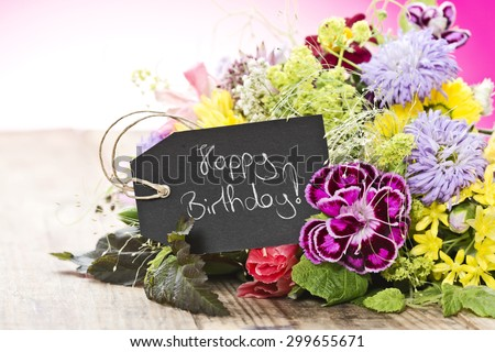 "a bouquet of flowers with a tag saying: ""Happy Birthday"""