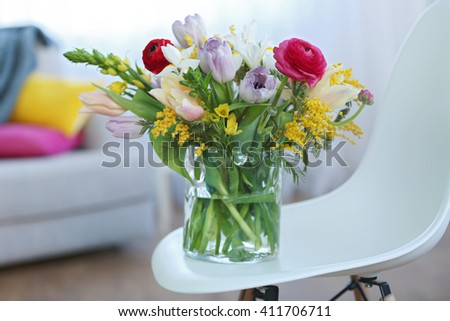 A bouquet of fresh flowers in a glass vase. - stock photo