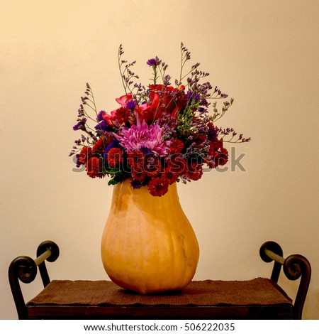 a bouquet of red and pink flowers in the vase made of pumpkin