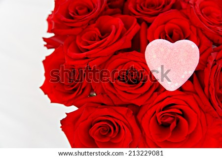 A bouquet of red roses to the right of the frame with a pink heart on top of them on isolated on a white background.  Room for copyspace.