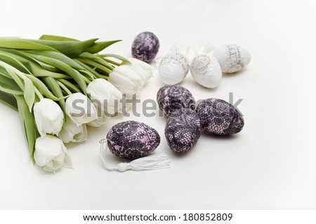 A bouquet of white tulips next to the decorated Easter eggs on a light background is. The image was photographed in the landscape format.