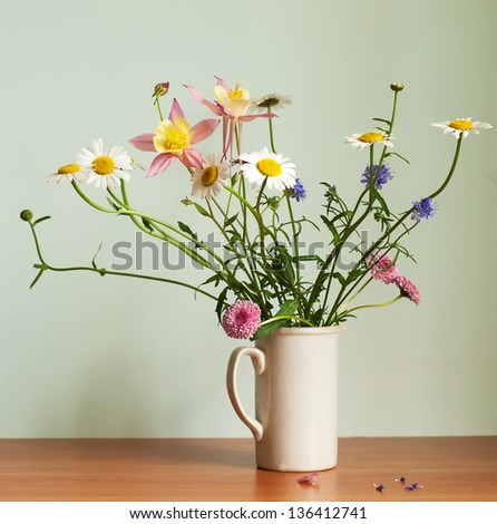 A bouquet of wildflowers in a country style vase - stock photo