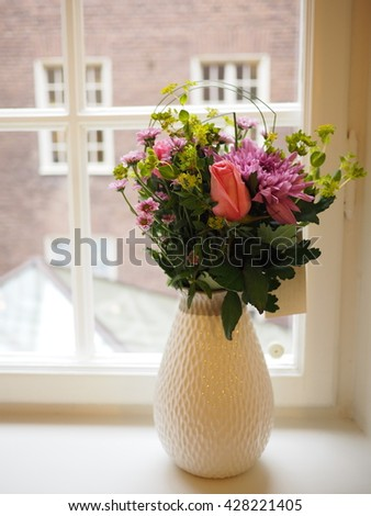 a bouquet with pink flowers in a vase by the window
