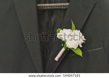 A boutonniere on the lapel of the suit.