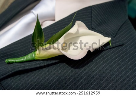 A boutonniere pinned to a man's suit jacket. - stock photo