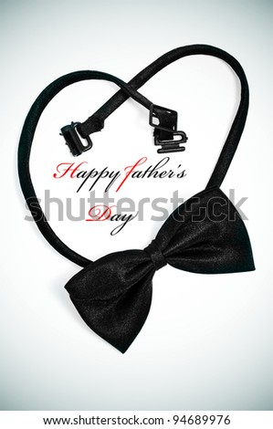a bow tie forming a heart and the sentence happy fathers day - stock photo