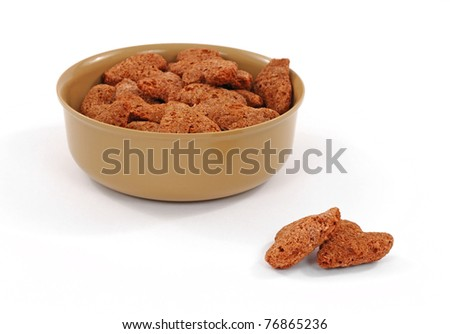 A bowl filled with crunchy beef and liver flavored dog snacks and two separate treats in front on a white background. - stock photo