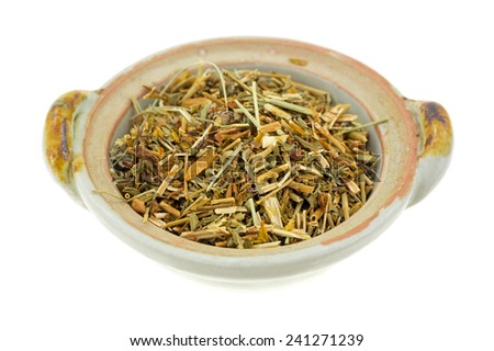 A bowl filled with shredded St. Johns Wort herb on a white background. - stock photo