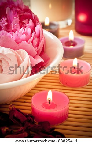 A bowl full of beautiful pink aromatherapy flowers with candles. Spa scene. - stock photo