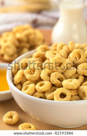 A bowl full of honey flavored cereal loops (Selective Focus, Focus on the standing cereal loop in the middle of the bowl)