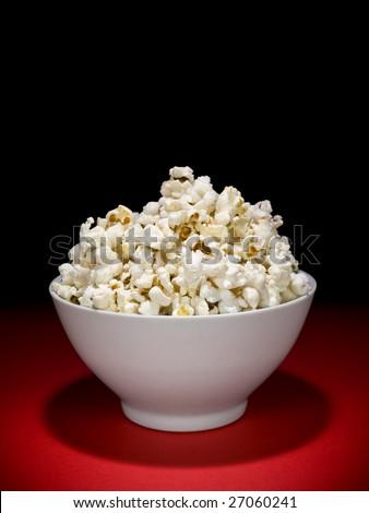 A bowl full of popcorn under the spotlight. - stock photo
