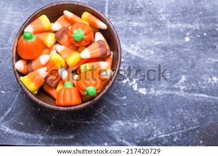 A bowl full of seasonal Halloween candy corn, a traditional fall treat. - stock photo
