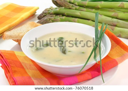 a bowl of asparagus soup with fresh ingredients - stock photo