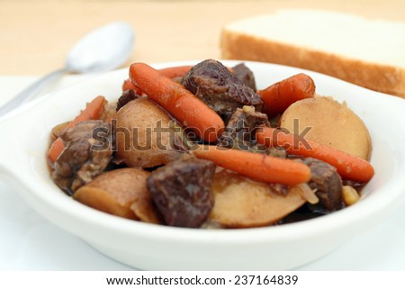 A bowl of beef stew with beef, carrots,potatoes, and onion. - stock photo