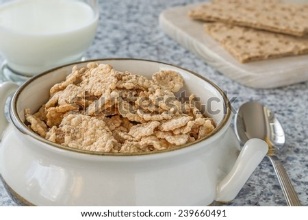 A bowl of bran flakes cereal on the breakfast table - stock photo