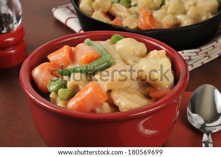 A bowl of chicken and dumplings with green beans and carrots