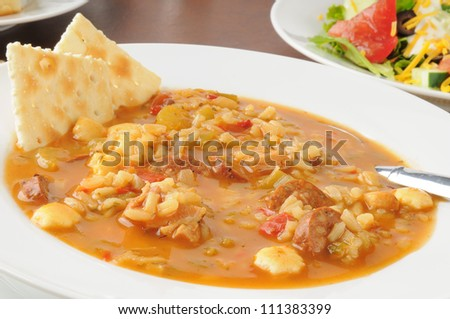 A bowl of chicken and sausage gumbo soup with a salad - stock photo