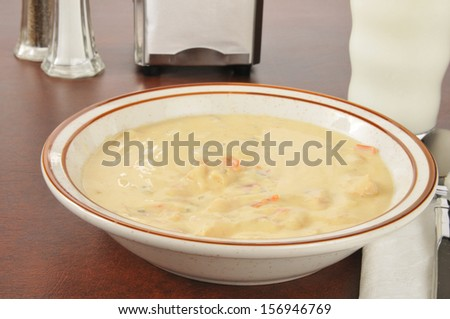 A bowl of chicken con queso soup with a glass of milk