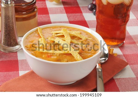 A bowl of chicken tortilla soup with a glass of iced tea