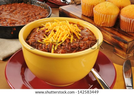 A bowl of chili con carne with cheddar cheese and cornbread muffins - stock photo