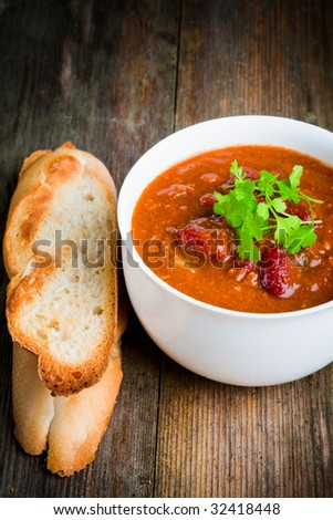 A bowl of chili con carne with toasted baguette and coriander