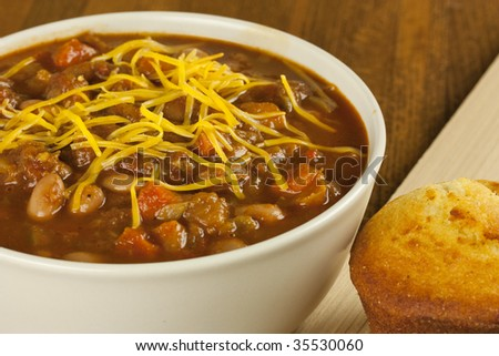 A bowl of chili with cheese on top and some cornbread on the side - stock photo