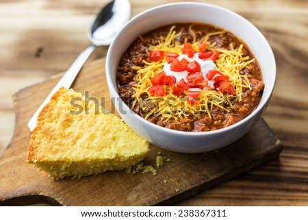 A bowl of chili with tomatoes, sour cream, cheese and a piece of cornbread against a wooden background.  - stock photo