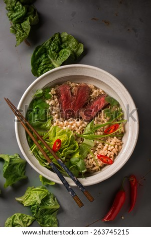 A bowl of Chinese ramen noodles with beef, Chinese cabbage, chili pepper, coriander and green onion, top view - stock photo