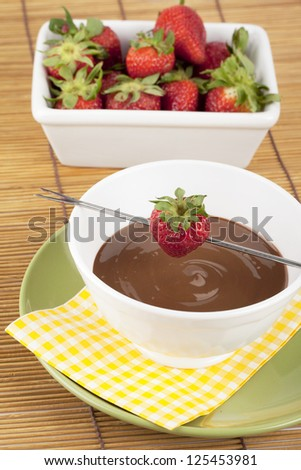 A bowl of chocolate fondue and fresh strawberries with stick - stock photo