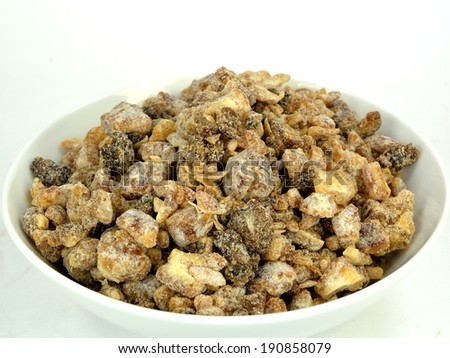 A bowl of chopped dates on a white background.