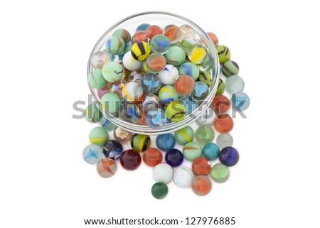 A bowl of colorful marbles with scattered swirl marbles - stock photo