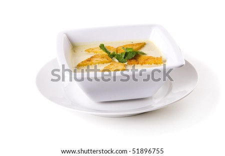 A bowl of cream soup, garnished with parsley and toast