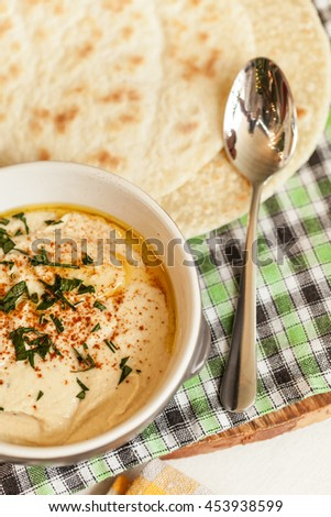 A bowl of creamy hummus with olive oil and pita chips. - stock photo