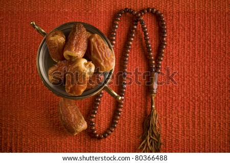 A bowl of dates and an Islamic rosary on a red rug - stock photo