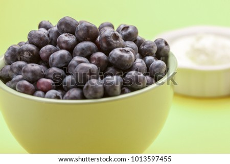 A bowl of delicious blueberries along with a bowl of whipped cream.