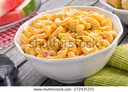 A bowl of delicious creamy macaroni and cheese salad on a rustic picnic table with watermelon and corn. - stock photo