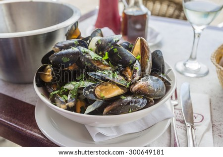 A bowl of delicious moules mariniere (mussels) for lunch in a seafood restaurant in Brighton, East Sussex, UK - stock photo