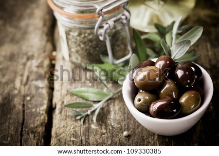 A bowl of fresh black olives and container of dried herbs stand on an old wooden kitchen table for use as ingredients in cooking - stock photo