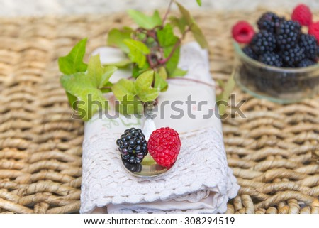 A bowl of fresh blackberries and raspberries with spoon over antique lace napkin and  wicker background.  - stock photo