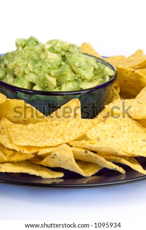 A bowl of fresh, chunky guacamole (avocados) and some yellow corn chips. - stock photo
