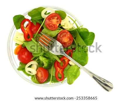 A bowl of fresh colorful salad and a fork isolated - stock photo