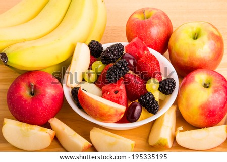 A bowl of fresh cut fruit with whole fruit - stock photo