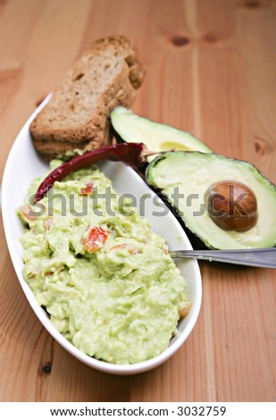 A bowl of fresh guacamole mexican food - stock photo