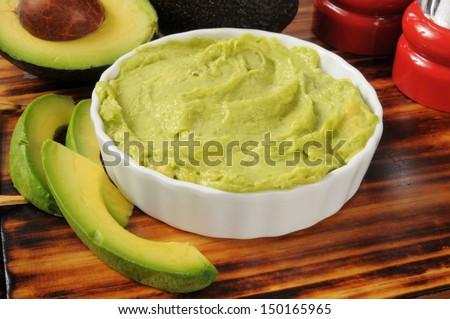 A bowl of fresh guacamole with fresh avocado - stock photo