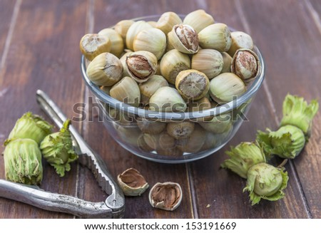 A bowl of fresh hazelnuts and a nut cracker on wooden table - stock photo