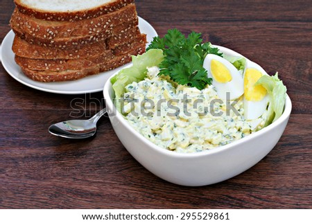 A bowl of fresh, homemade egg salad surrounded by lettuce and garnished with a hard boiled egg. - stock photo