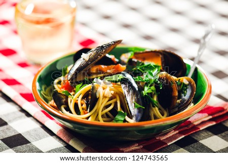 A bowl of fresh spaghetti with mussels. This traditional italian food is placed inside a green bowl and served on a table with a checkered tablecloth. - stock photo