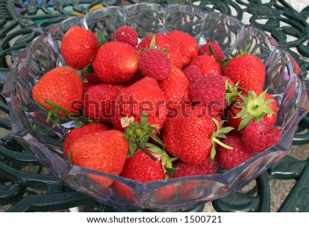 A bowl of fresh summer strawberries on green metal table. - stock photo