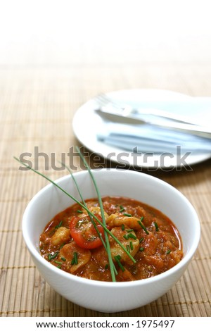 A bowl of freshly cooked king prawn masala on bamboo mat, with copyspace - stock photo