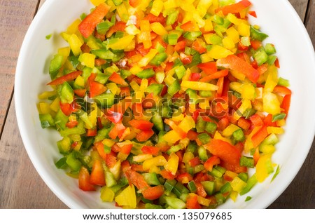 A bowl of freshly diced red yellow and green peppers - stock photo